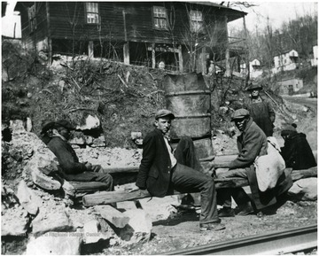 Men sitting on logs during the 1931 coal strike at Scott's Run, W. Va.