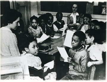 A group of Osage School children in the 1940s and teacher, Mrs. Richard Smith (left hand corner.) Osage School was located in Osage, West Virginia, Monongalia County.  Mrs. Smith may have been visiting the classroom as African-American teachers were employed by the segregated school at this time.For information on the Mountaineer Mining Mission see A&M 2491 (SC).