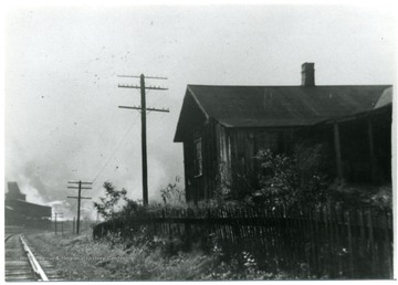 House with picket fence separating it from the railroad tracks.