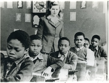 "School children of the Osage School in the 1940s and their teacher. For information of the Mountaineer Mining Mission, see A&M 2491 (SC).L to R: Tommy Wells (deceased), Sammy Dobbs (lived in Jerome Park for ling time, shot to death), Wesley Morton, Jimmy Summervile, unidentified, ""Snookie"" Williams.Teacher most likely someone who came for a special mission, possibly Mountaineer Mining Mission."