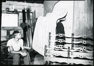 Man sits in a chair next to mattress, bed frame, and other items at the Scott's Run Reciprocal Economy Salvage building.