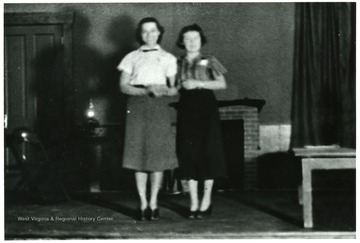 Two women standing inside of a house.