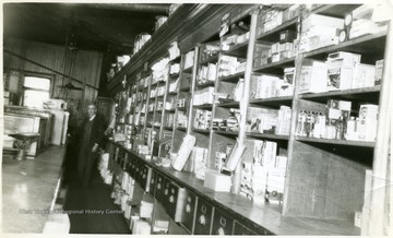 Shelves with stocked store merchandise. Mr. Guinn is standing in the background of the picture.