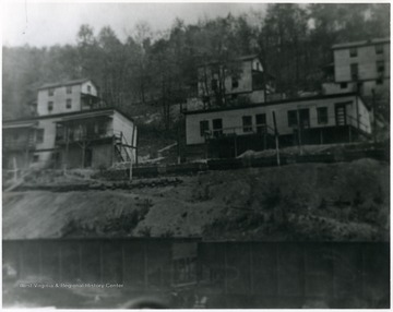 Miner's homes on a hillside above train cars. 'For more information on Mountaineer Mining Mission see A&M 2491 (S.C.)'