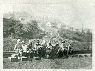 A group of children sitting on railroad tracks, with homes in the background.  'For more information on Mountaineer Mining Mission, see A&M 2491 (S.C.)'