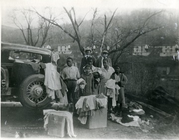 African-American family stand beside a car holding clothing. 'For more information on Mountaineer Mining Mission, see A&M 2491 (S.C.)'