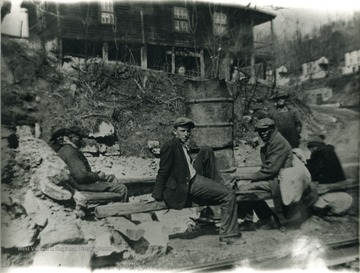 A group of men sitting on a wooden post. 'For more information on Mountaineer Mining Mission, see A&M 2491 (S.C.)'