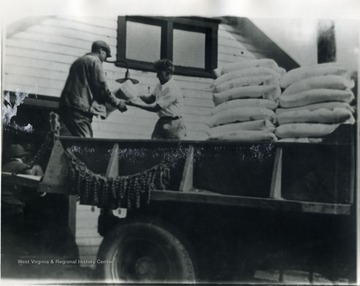 Two men move sacks of flour from the bed of a truck. 'For more information on Mountaineer Mining Mission, see A&M 2491 (S.C.)'