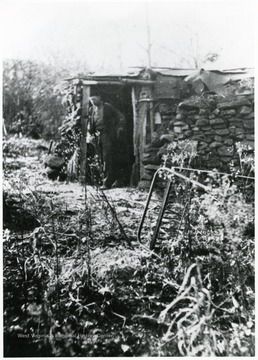 Man standing in doorway to old house.