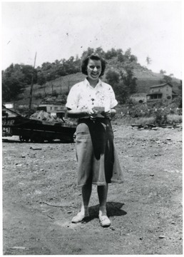 Woman smiling for picture. There is a house in the background.
