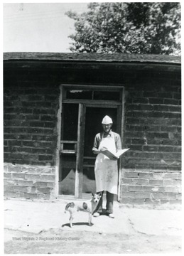 Baker wearing white apron and hat with dog at his feet.