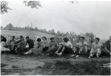 A group sitting on the outskirts of a garden, possibly American Friends Service Committee workers.