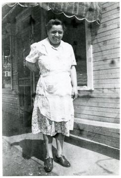 Sylvia Viola standing outside of house.