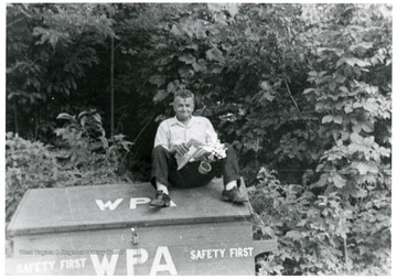 Pete Viola sitting on a wooden box with lid.