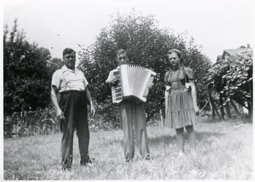 The Viola family standing in the grass with Tullio holding a accordion.