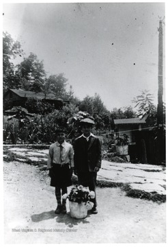 Two boys stand with a flower pot.