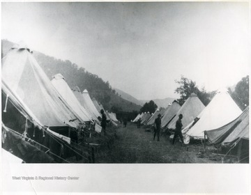 Soldiers stand between rows of tents. Troops Commanded by Gen. Bandholtz.