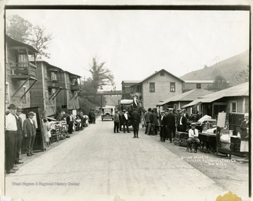Miners and their belongings line the street below company houses.