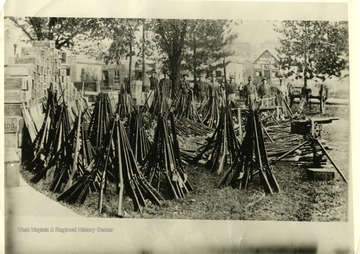 'Arms and ammunition surrendered to or captured by state troops immediately after first declaration of martial law on Paint Creek and Cabin Creek, September 2, 1912. See book, page 32, etc. Picture used on page 32 of book by H. B. Lee. Rifles, machine guns, pistols, and ammunition seized by the militia in the strike zone. Boxes on the left contain 225,000 rounds of machine gun ammunition.'