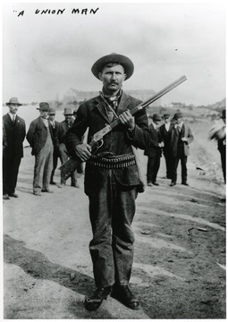 A union man standing with his rifle and ammunition.  Other men standing behind him.