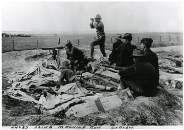 Men using a machine gun and sitting in surrounding area with guns.