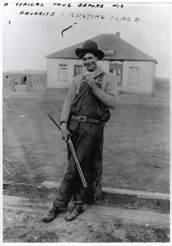 A man standing with his gun leaning against a post, Saloon in the background.