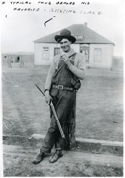 A man with a gun leaning against a post, saloon in background.