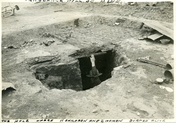 Man standing in a hole in the ground where eleven children and 2 women burned alive during the Ludlow Strike.