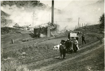 Men surround a white flag while the remains of building smolder in the background.