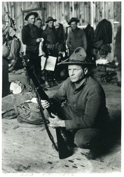 A man kneeling with his rifle.  Other men standing in the background.