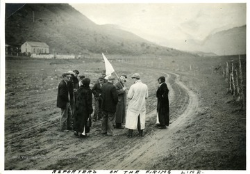 Men and women standing on a firing lane holding a white flag.