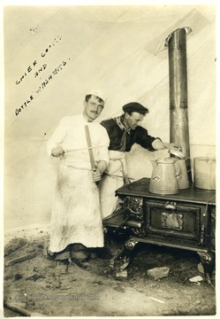 Two men working over a stove.