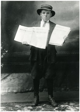 Young boy holding two copies of the newspaper The Miner's Herald.  Headline reads: 'Miners! Do Not be deceived.  Terrible strike is in Colorado.'