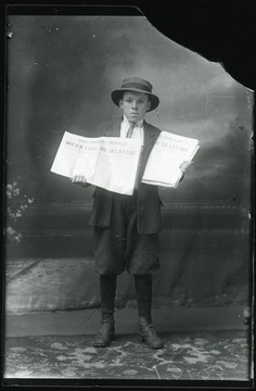 Young boy holding two copies of a The Miner's Herald newspaper, published in Montgomery, W.Va.  The headline reads:  Miners! Do Not be Deceived.  Terrible Strike is on in Colorado.  Copies dated Friday, Oct. 24, 1913.