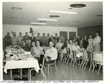 Group portrait of committee members standing and seated at tables during the W.E. Campaign, Volunteer Organization Committee meeting in Oklahoma City, Ok.