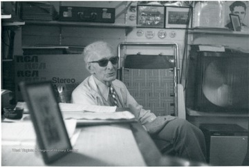 Unidentified man with sunglasses on seated at a table.