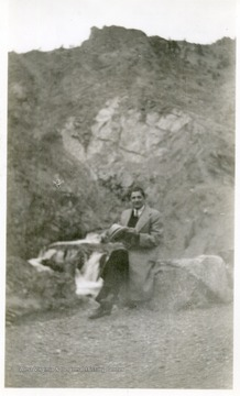 Joe Ozanic sitting on a rock on a hillside.