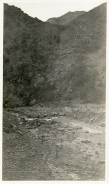 Creek with rocks visible beside a hillside.
