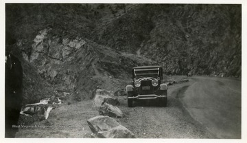 Car parked along road beside a hillside.  Man standing on the side of the picture.