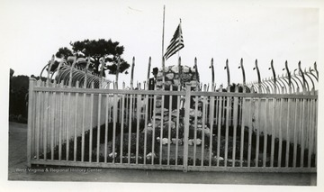 Men standing around a fenced in memorial/grave.