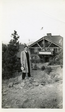 Joe Ozanic standing in front of building with a flag on the roof top.