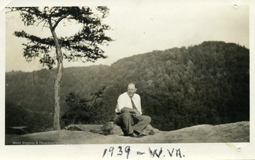 Ben Kunz sitting on a rock.  Mountains in the background.