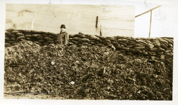 Man standing in front of sandbags at the Wasson air shaft.