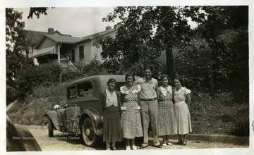 Four women and one man standing behind a car. Photograph from Joe Ozanic scrapbook.