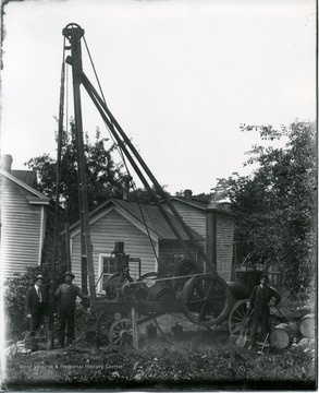 Men pose by drilling equipment. 'Rig possible owned by O. C. Carter.'