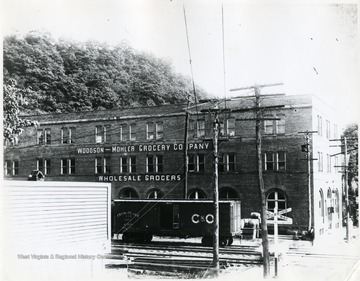 Frontal view of the Woodson - Mohler Grocery Co. Wholesale Grocers building in Alderson W. Va. with C&O boxcar situated in front of building.