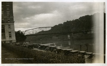 Cars parked in a parking lot beside a river. Photograph from Joe Ozanic scrapbook.