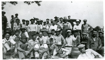 'The day is finished and refreshments are enjoyed by all. Best Union men that ever lived of No. 35, PMA, who gave their time and labor to build a memorial to clean unionship.' Miners at the Miners Cememtary, Mt. Olive, Ill.
