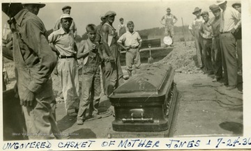 Workers stand around the uncovered casket of Mother Jones.