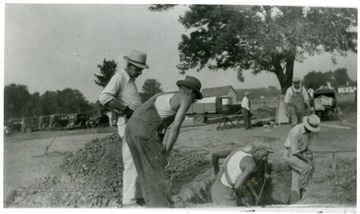 Men stand around the opening while men with shovels excavate the grave of Mother Jones.